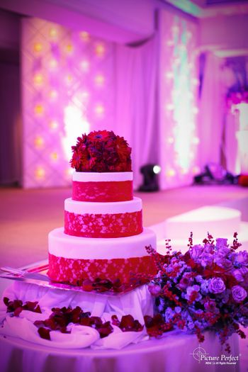 White and red three tier wedding cake with red flowers on top