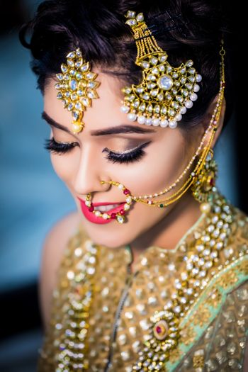 Photo of Bridal makeup with brown eyes and red lips with silver liner