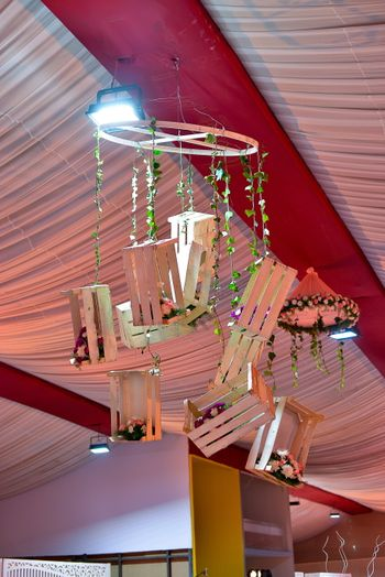Chandelier with hanging wooden crates and florals