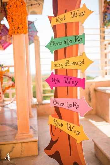 Photo of Mehendi or wedding decor with cute direction boards
