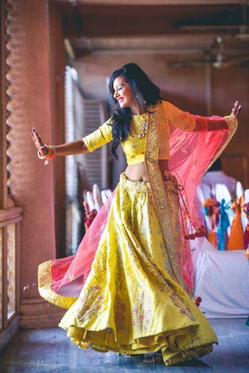 Photo of Happy dancing bride in yellow lehenga