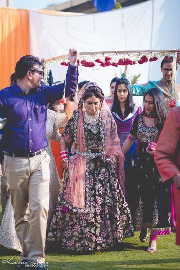 Bride in dark lehenga entering under phoolon ki chadar