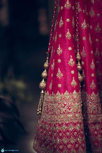 Simple pomegranate pink bridal lehenga with golden latkans