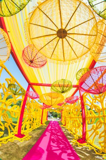 Hanging umbrellas in yellow and pink for mehendi entrance decor