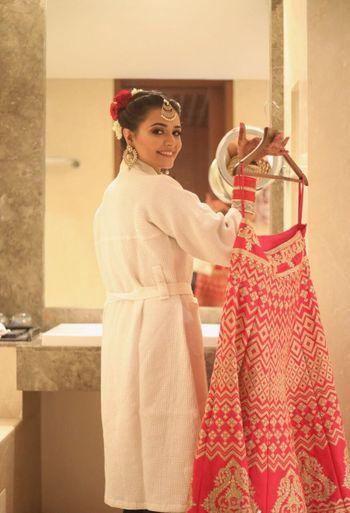 Bride in robe with lehenga on hanger