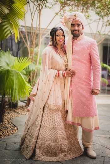 Bride and groom in matching light pink outfits