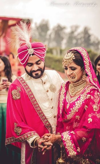 Bride and groom in bright pink outfits