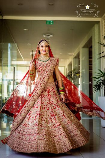 Bride twirling in red and gold lehenga with green jewellery