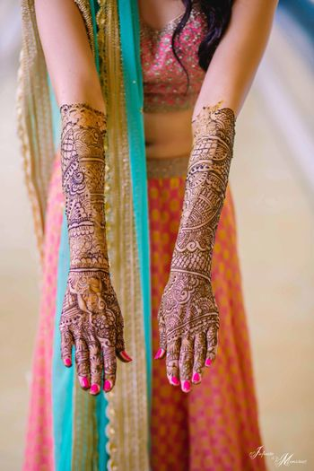 Bridal hands showing off mehendi till elbow