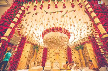 Elaborate red and white mandap with hanging floral strings