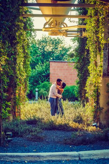 Photo of Outdoor pre wedding shoot with couple kissing shot