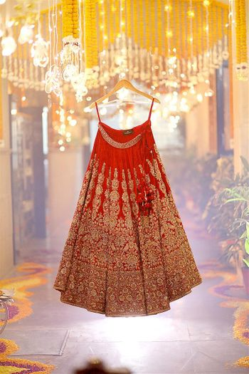 Red and gold bridal lehenga skirt on hanger