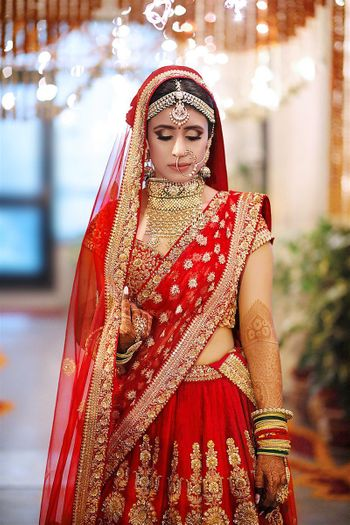 Bride in red and gold lehenga with double dupatta