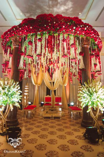 Photo of Floral mandap idea with red and gold decor and hanging strings