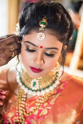 South Indian bridal makeup with gold eyes and red lips