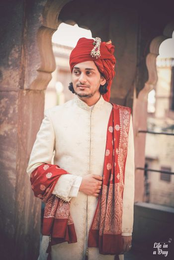 Off white sherwani with red safa and stole