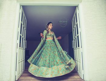 Bride twirling in green mehendi lehenga