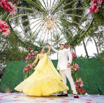 Twirling bride shot in pretty yellow lehenga