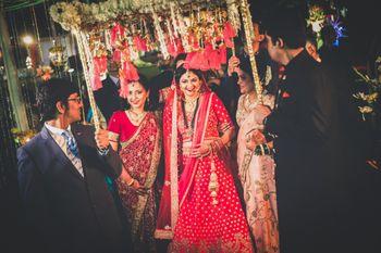 Bride entering under matching phoolon ka chadar