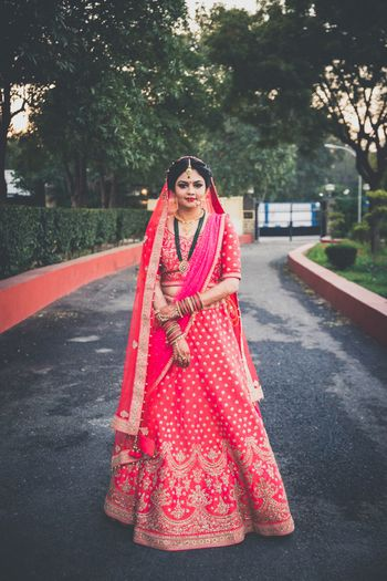 Red and gold bridal lehenga with long green necklace