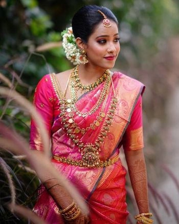 South Indian Bride wearing a pink silk saree with temple jewellery.