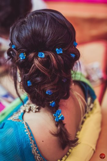 Mehendi hairstyle braid with tiny blue flowers