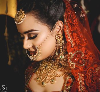 Unique gold choker with bridal nath and maangtikka