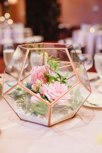 Photo of Brass and glass terrarium with flowers