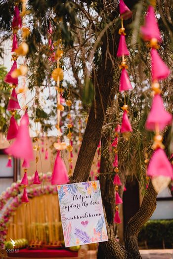 Photo of Mehendi decor with tassels and hashtag board