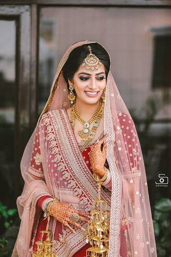 Bride in red lehenga with light pink dupatta