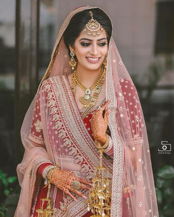 Bride in red lehenga with lighter dupatta