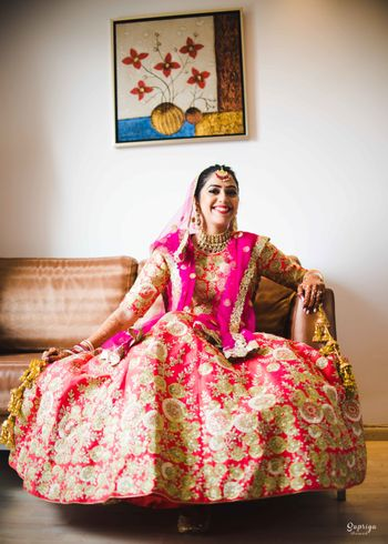 Happy bride in bright pink and gold lehenga