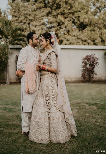 Offbeat bridal lehenga in ivory with matching groom