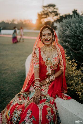 Happy bride shot in lehenga with unique motifs