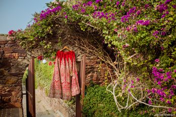 Red bridal lehenga on hanger outdoors