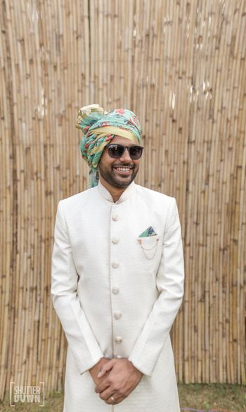 Contrasting groom accessories with white sherwani