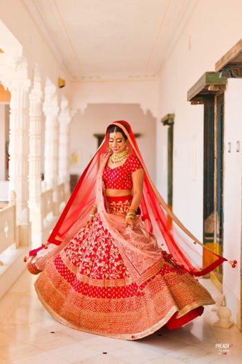 Photo of Simple red bridal lehenga twirling bride
