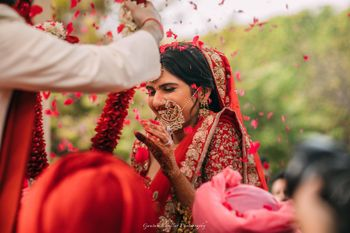 Happy bride in red during jaimala shot