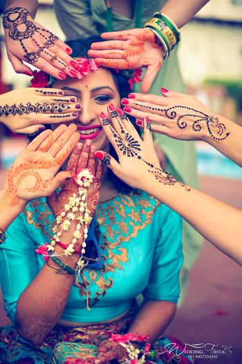 Bride with bridesmaids showing off mehendi portrait