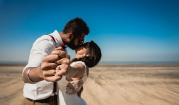 Proposal kissing shot showing off engagement ring