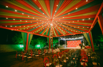 Bright and colourful mandap with drapes and fairy lights