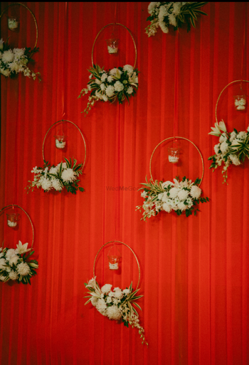 Red backdrop with floral wreaths and candles