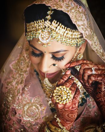 Photo of A beautiful bride with gold makeup and gold jewellery.