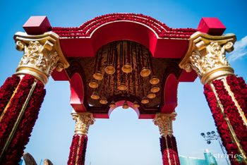 Photo of Traditional red roses laden mandap with brass bells