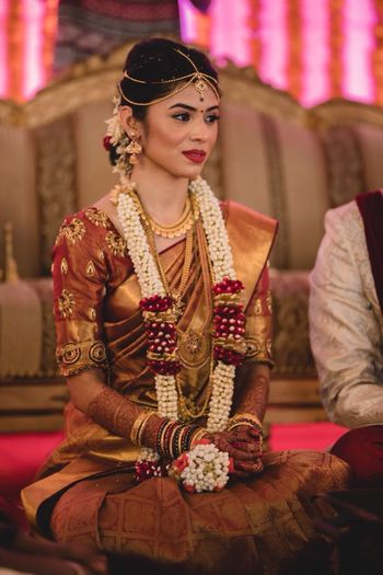 Dull gold and maroon bridal look for South Indian bride
