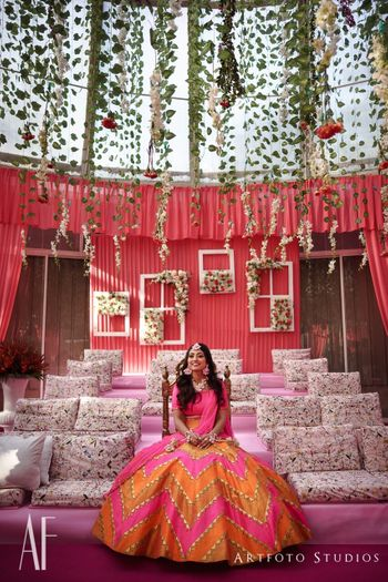 Photo of Mehendi decor with bright pink and hanging floral strings