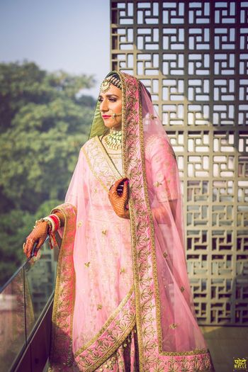 Photo of Stunning pastel pink bridal lehenga with gold work and a unique dupatta drape in triangle