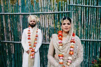 Colourful roses jaimala against ivory bride and groom outfits