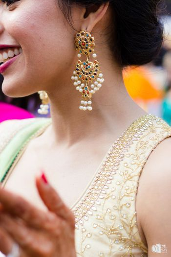 Bride wearing colourful earrings for mehendi with pearls