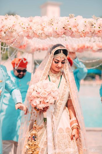 Beautiful bridal entry with peach lehenga and bouquet